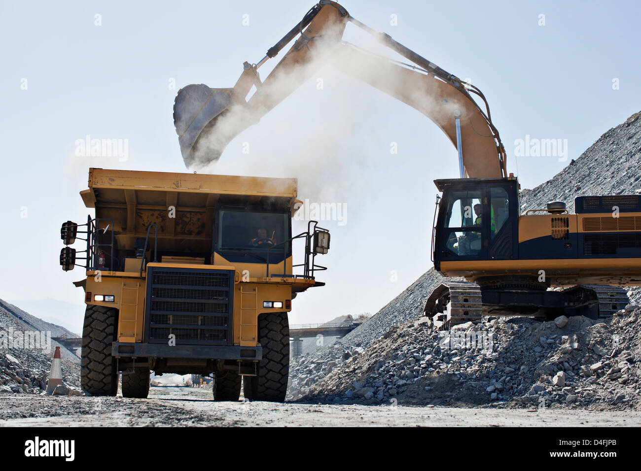 Digger and truck working in quarry - Stock Image