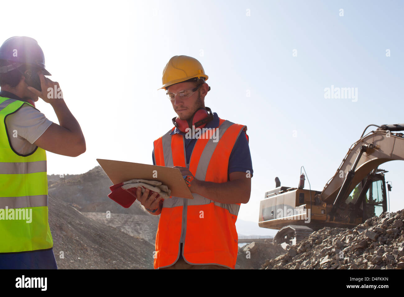 Workers standing in quarry - Stock Image