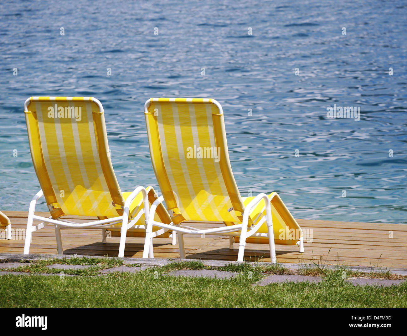 The picture shows two white-and-yellow deck chairs by the waterside ...