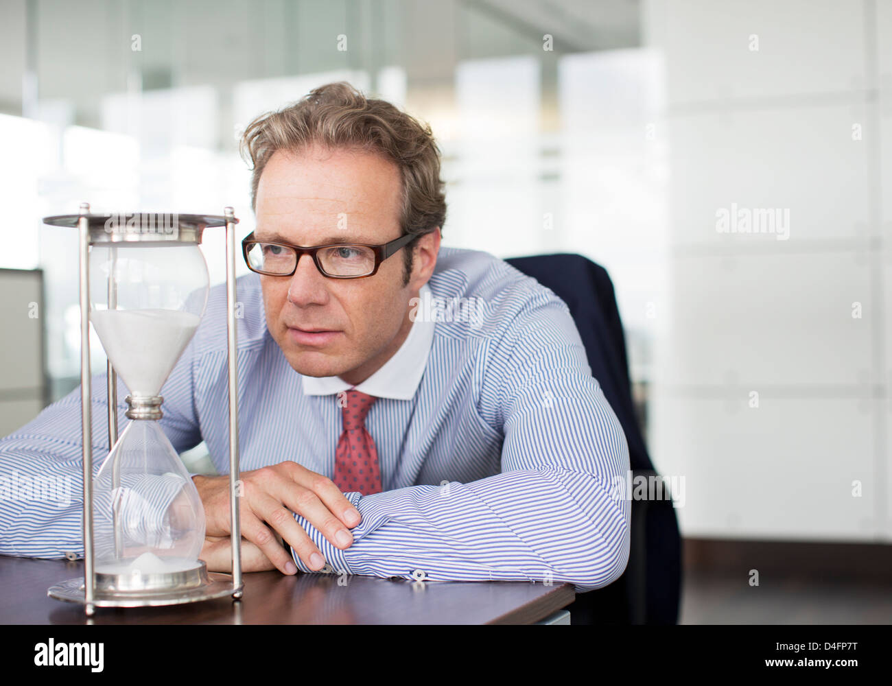 Businessman watching hourglass at desk - Stock Image