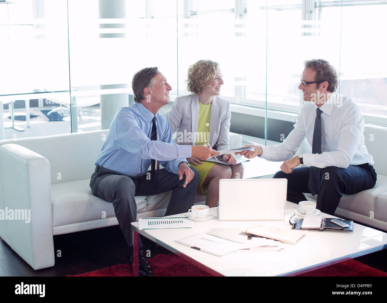 Business people talking office lobby area - Stock Image