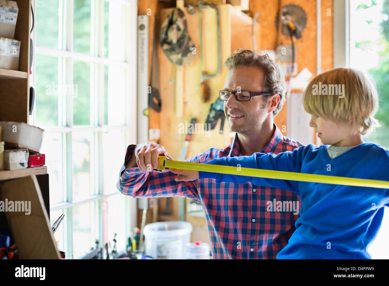 Father and son working in garage - Stock Image