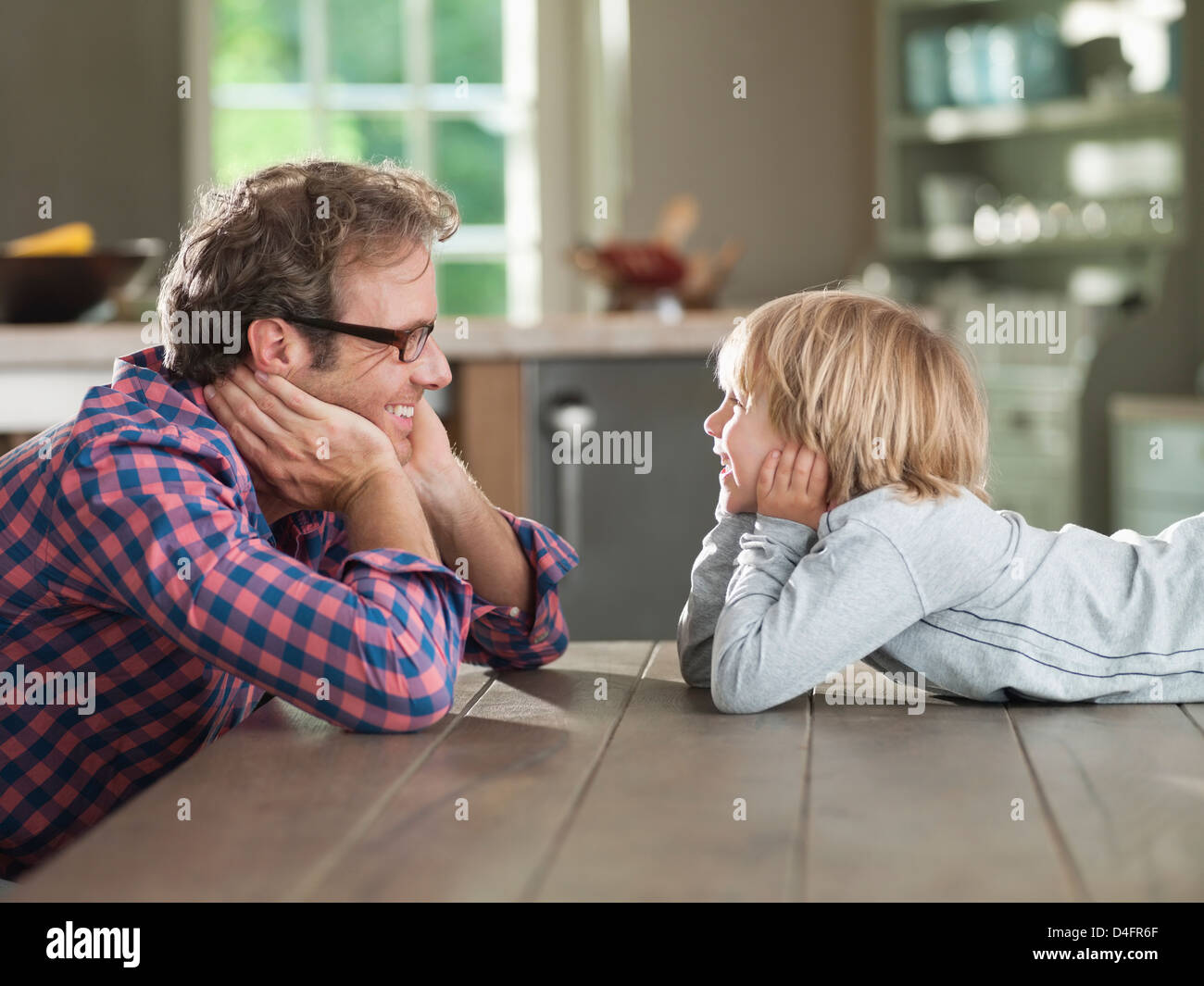 Father and son admiring each other at table - Stock Image