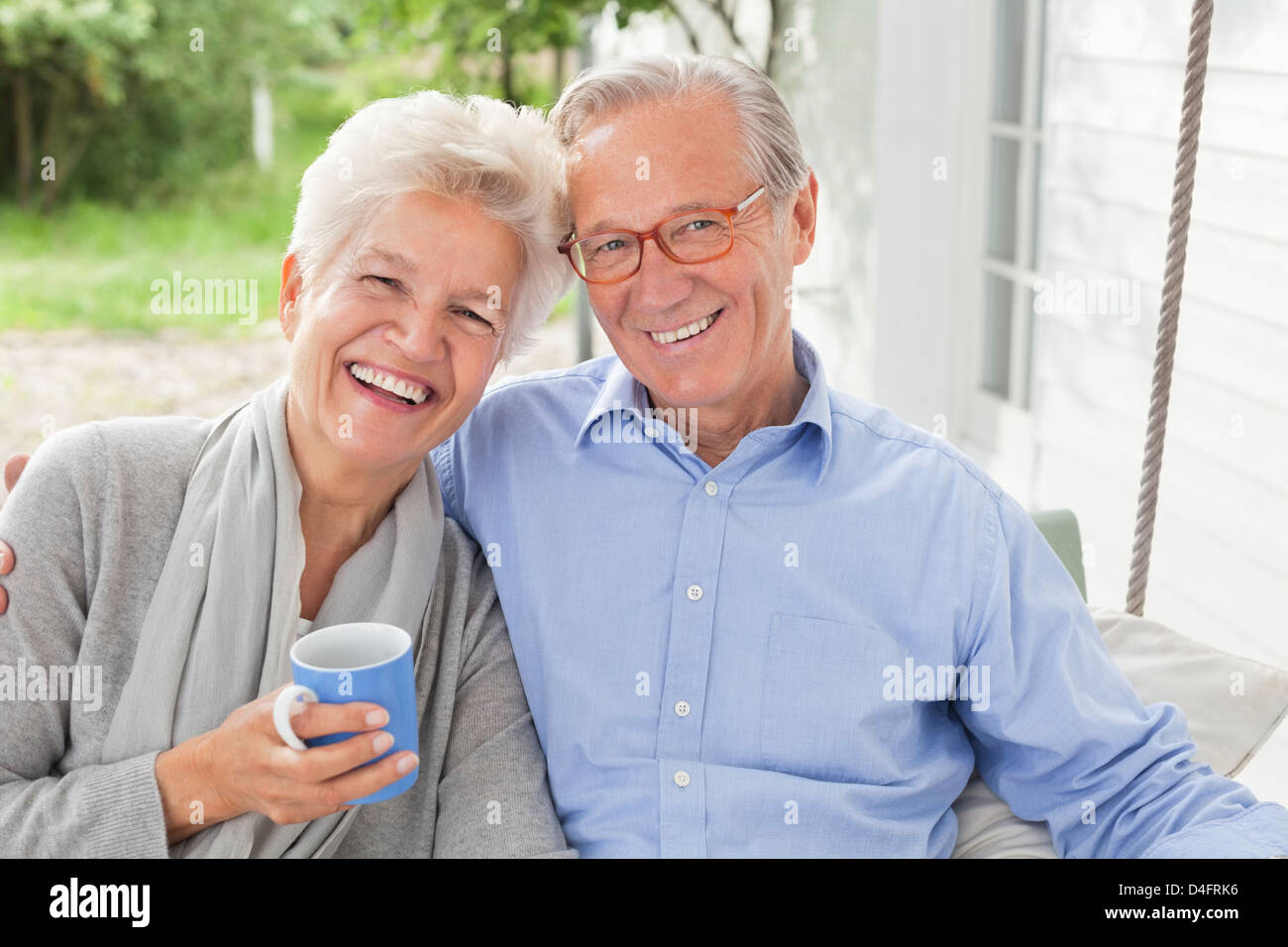 Smiling couple sitting on porch swing - Stock Image