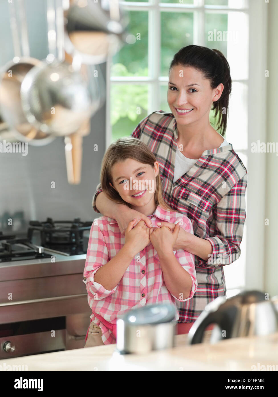 Woman hugging daughter in kitchen - Stock Image