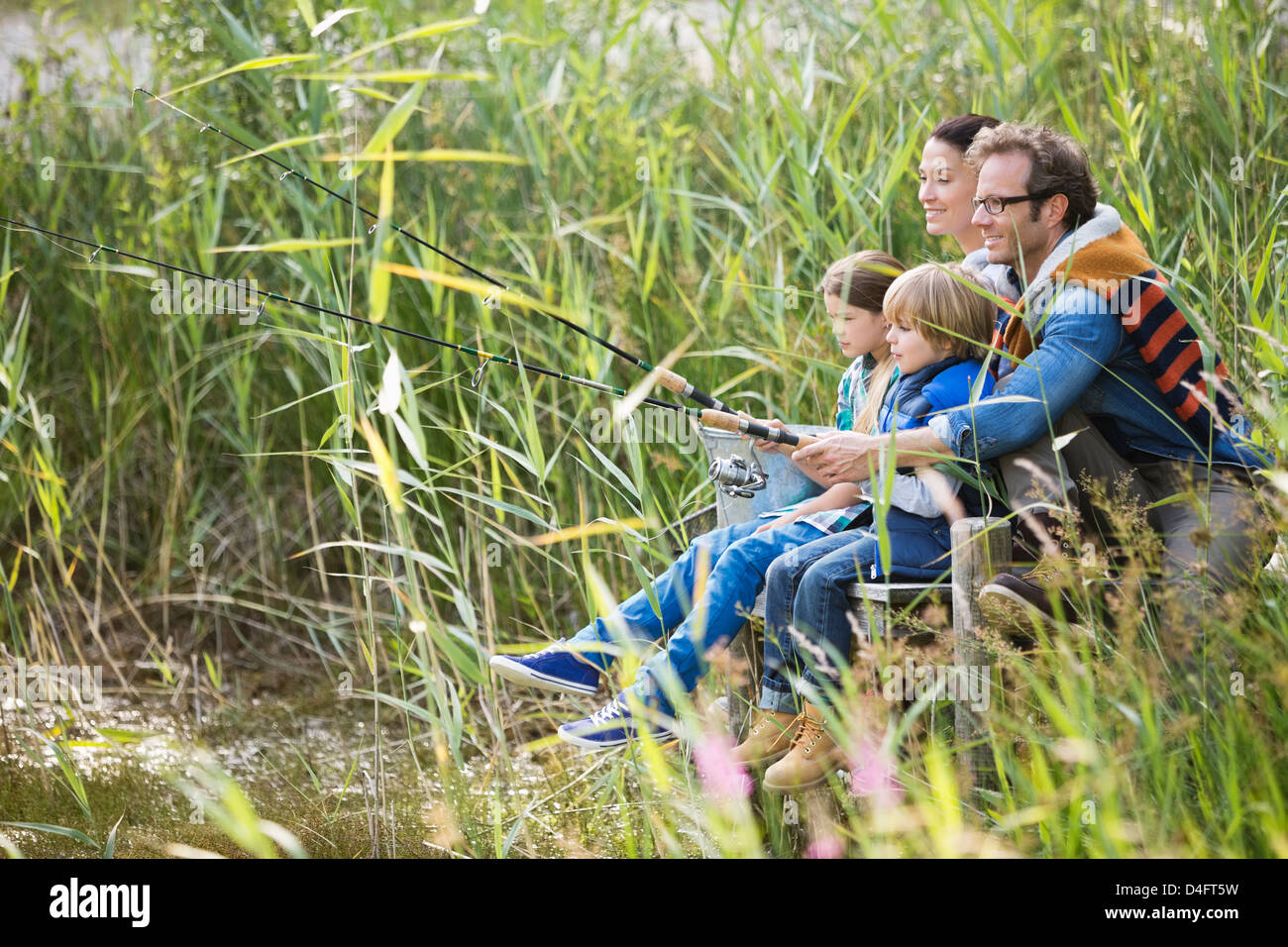 Family fishing together in tall grass - Stock Image