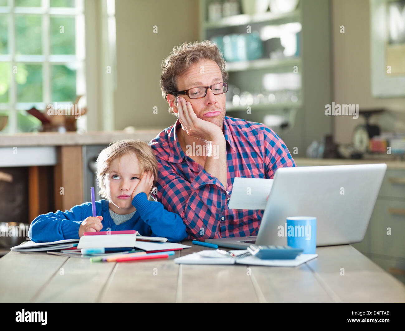 Bored father and son working at table - Stock Image