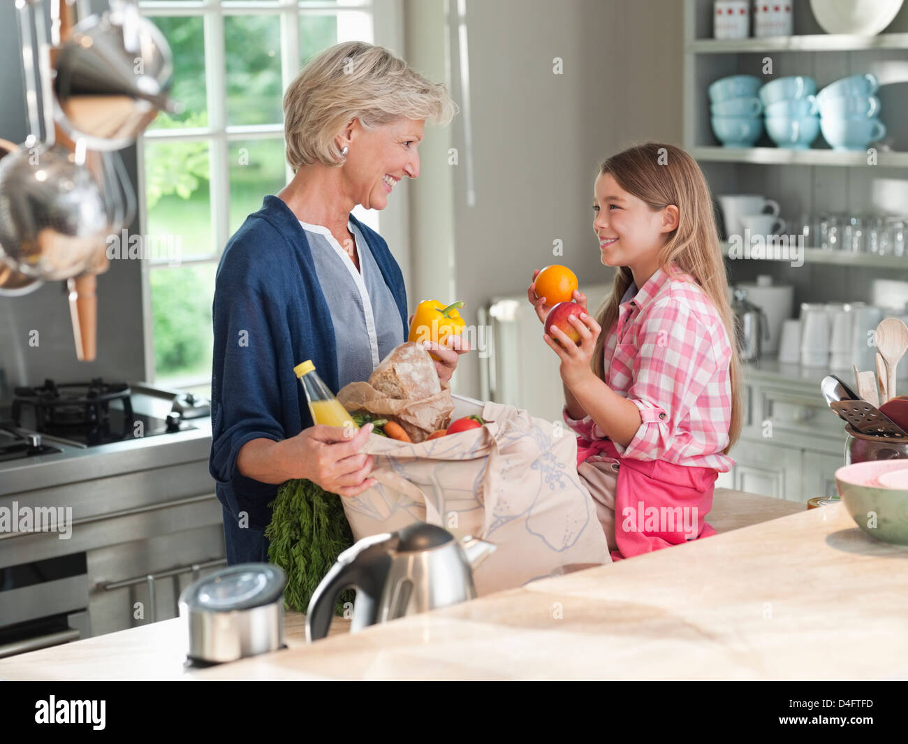 Woman and granddaughter unloading groceries - Stock Image
