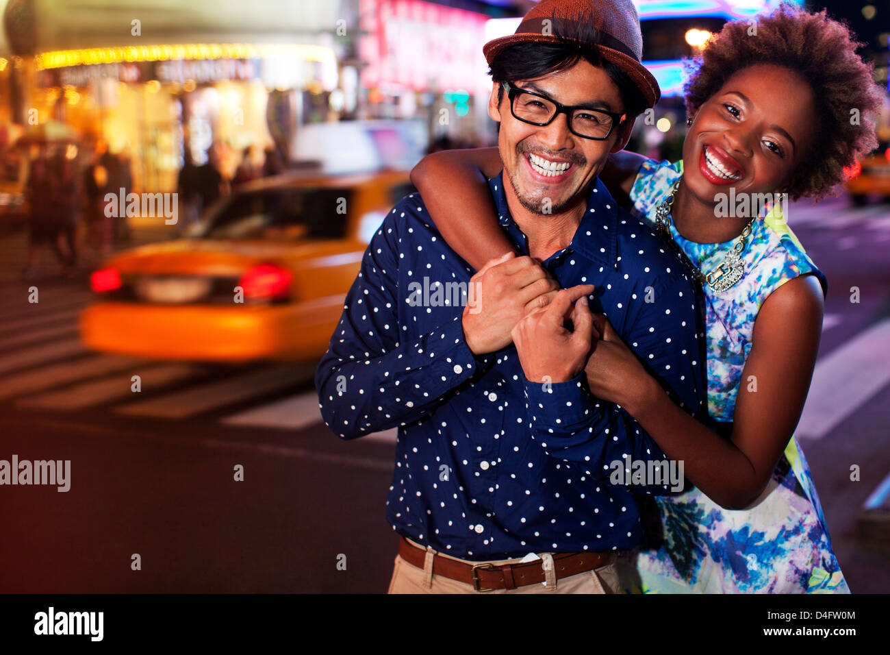Couple smiling on city street at night - Stock Image