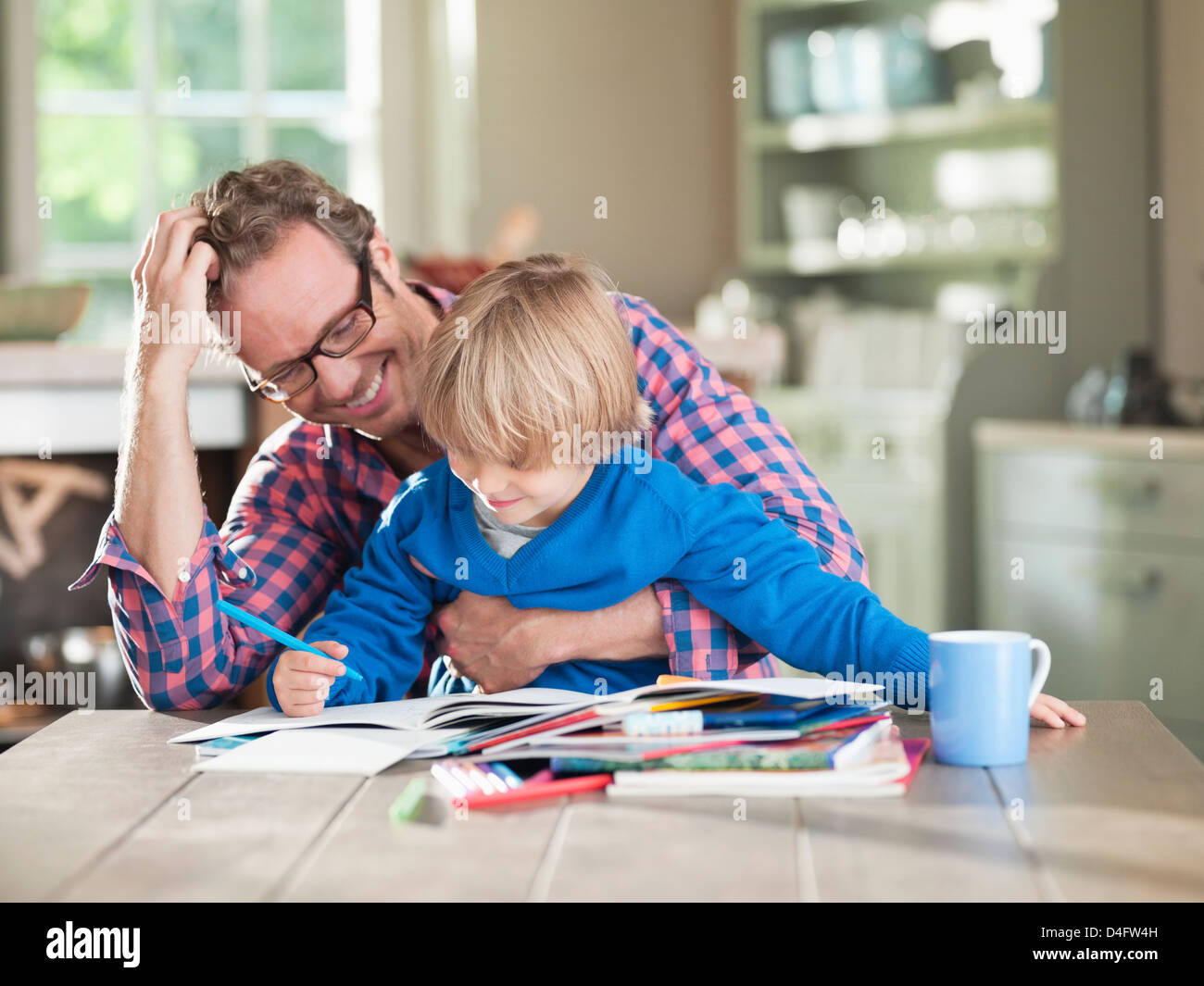 Father and son doing homework at kitchen table - Stock Image