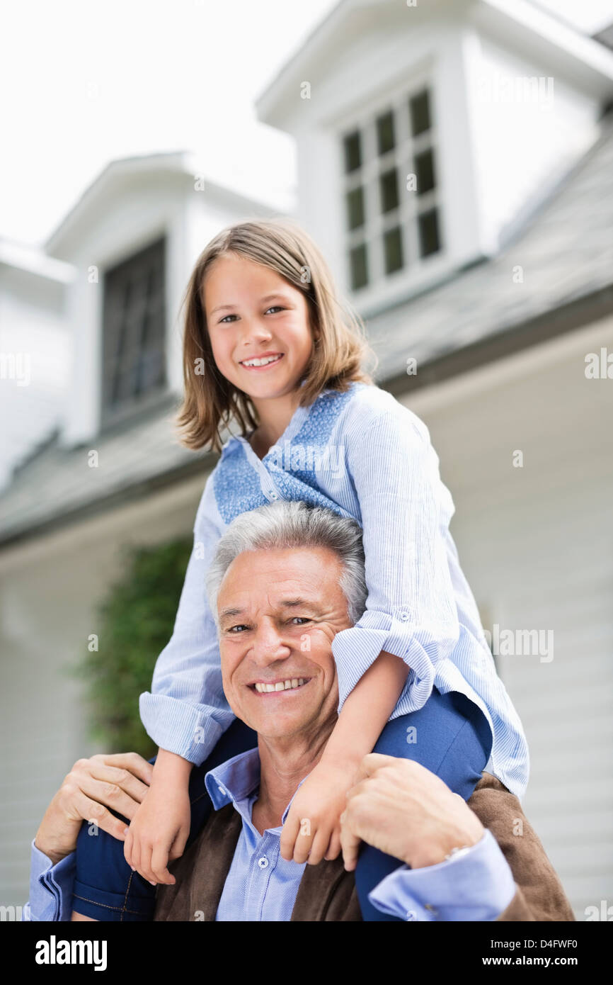 Man carrying granddaughter on shoulder outdoors Stock Photo