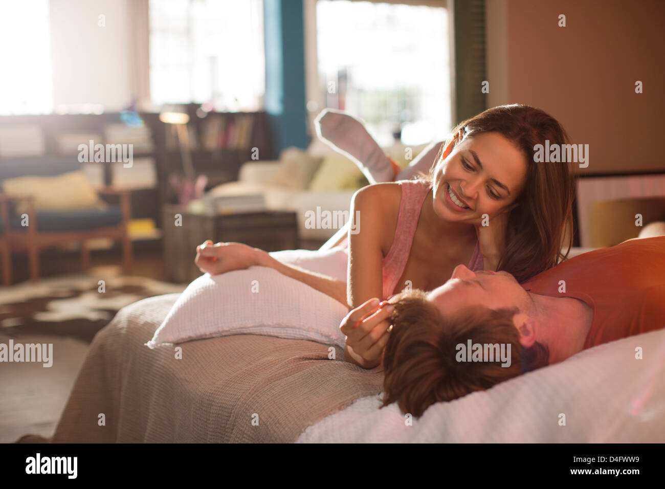 Couple relaxing on bed together - Stock Image