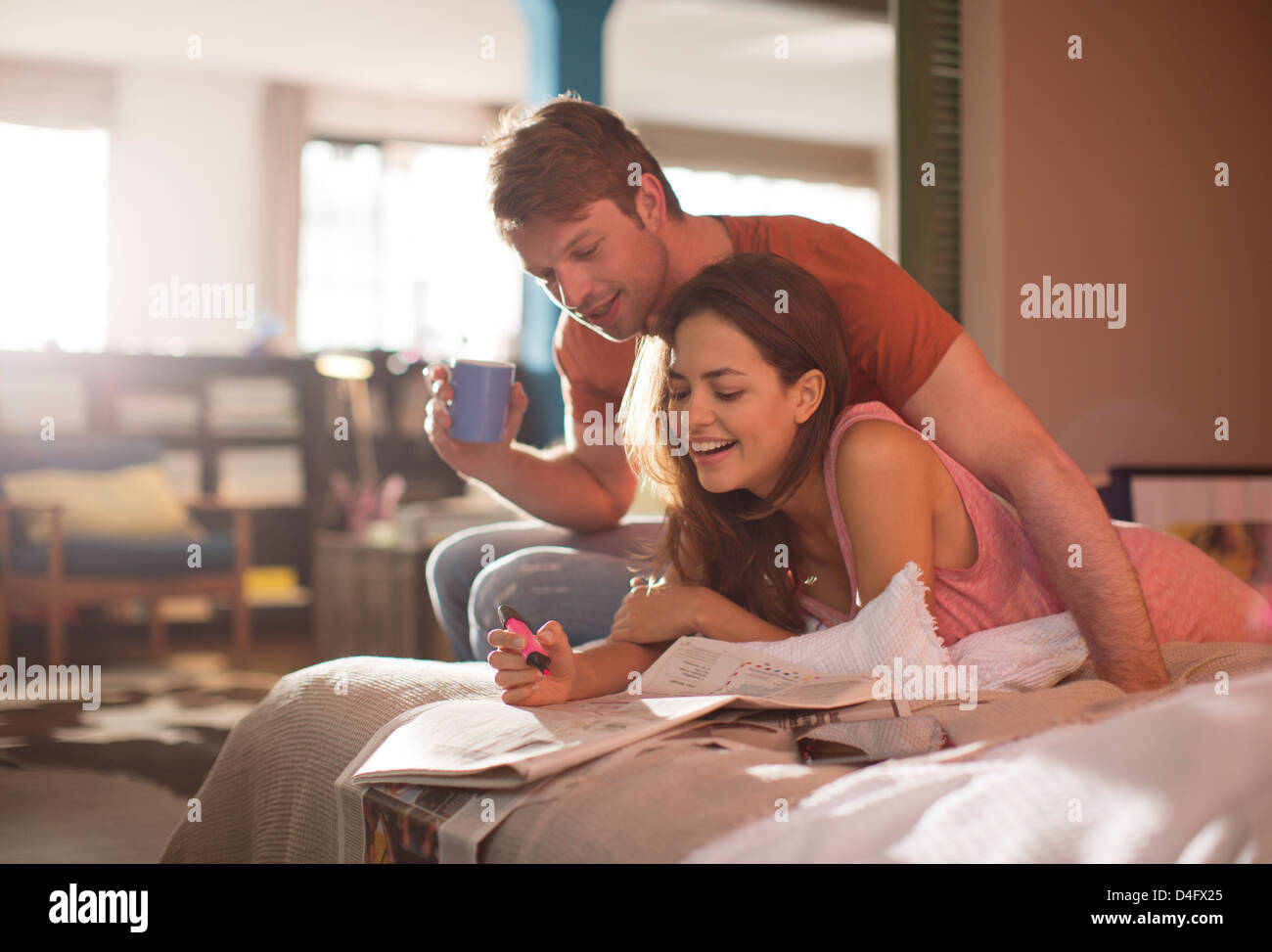 Couple reading newspaper together on bed - Stock Image
