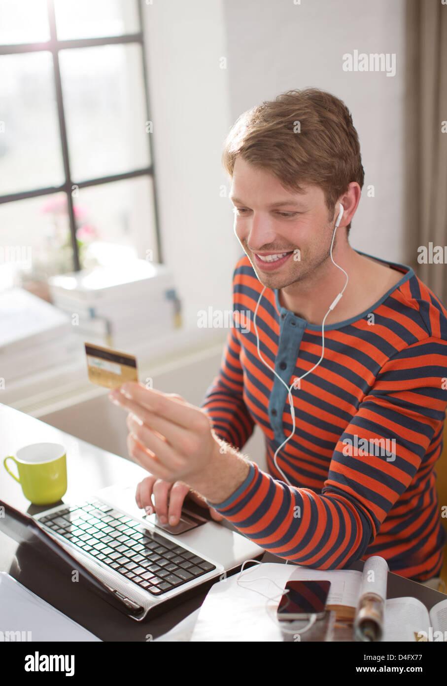 Man in headphones shopping on laptop - Stock Image