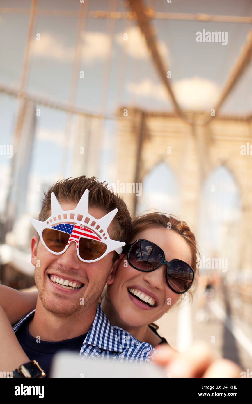 Couple in novelty sunglasses taking picture on urban bridge - Stock Image