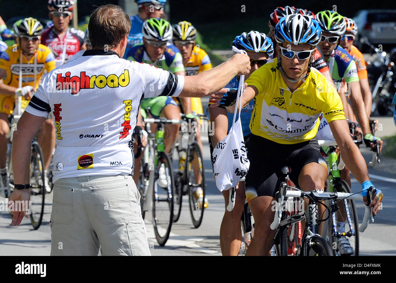 b610f052090 German cyclist Linus Gerdemann (R) of Team Columbia wears the Yellow jersey  as the overall leader and takes some supplies during the second stage of  the ...