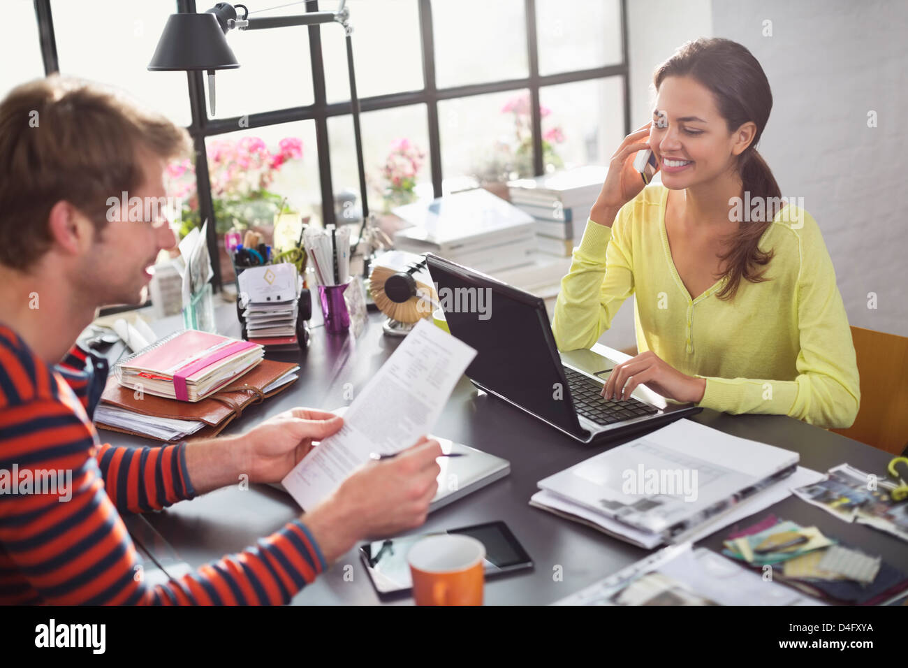 Couple working together at desk - Stock Image