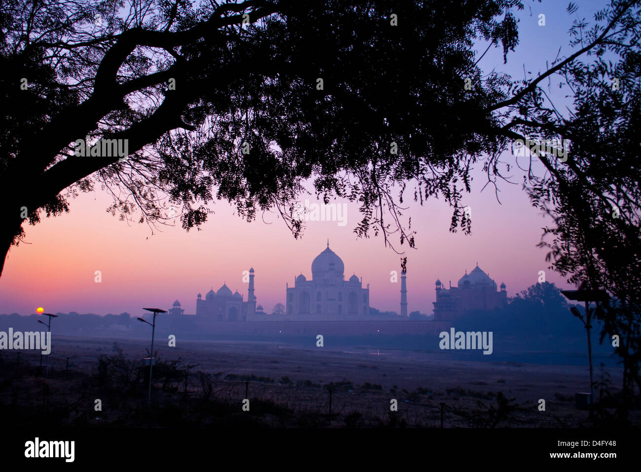 The Taj Mahal at sunrise, photographed from across the dried up river Yamuna, in Mehtab Bagh park - Stock Image