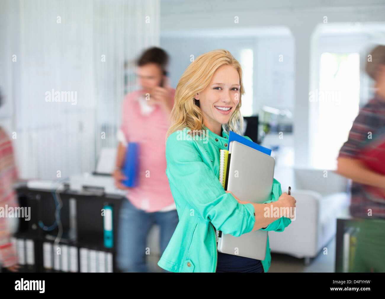 Businesswoman carrying folders in office - Stock Image