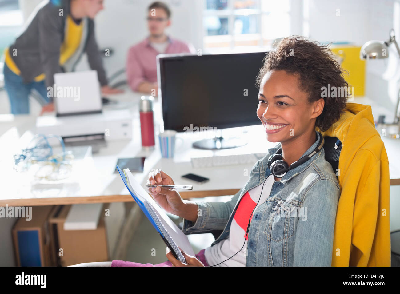 Businesswoman making notes at desk - Stock Image