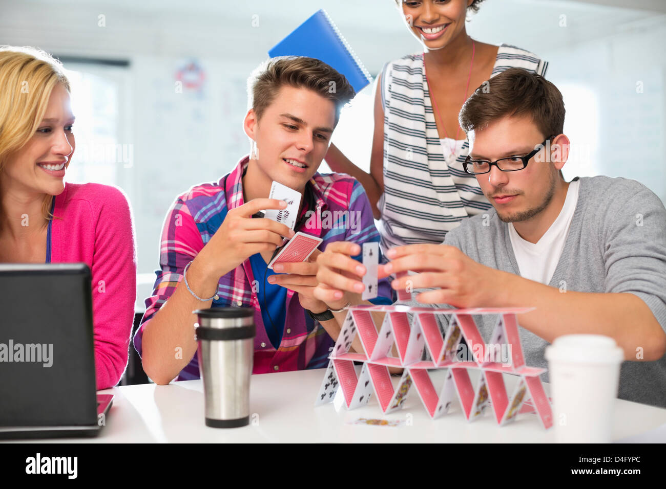 Business people making house of cards in office - Stock Image