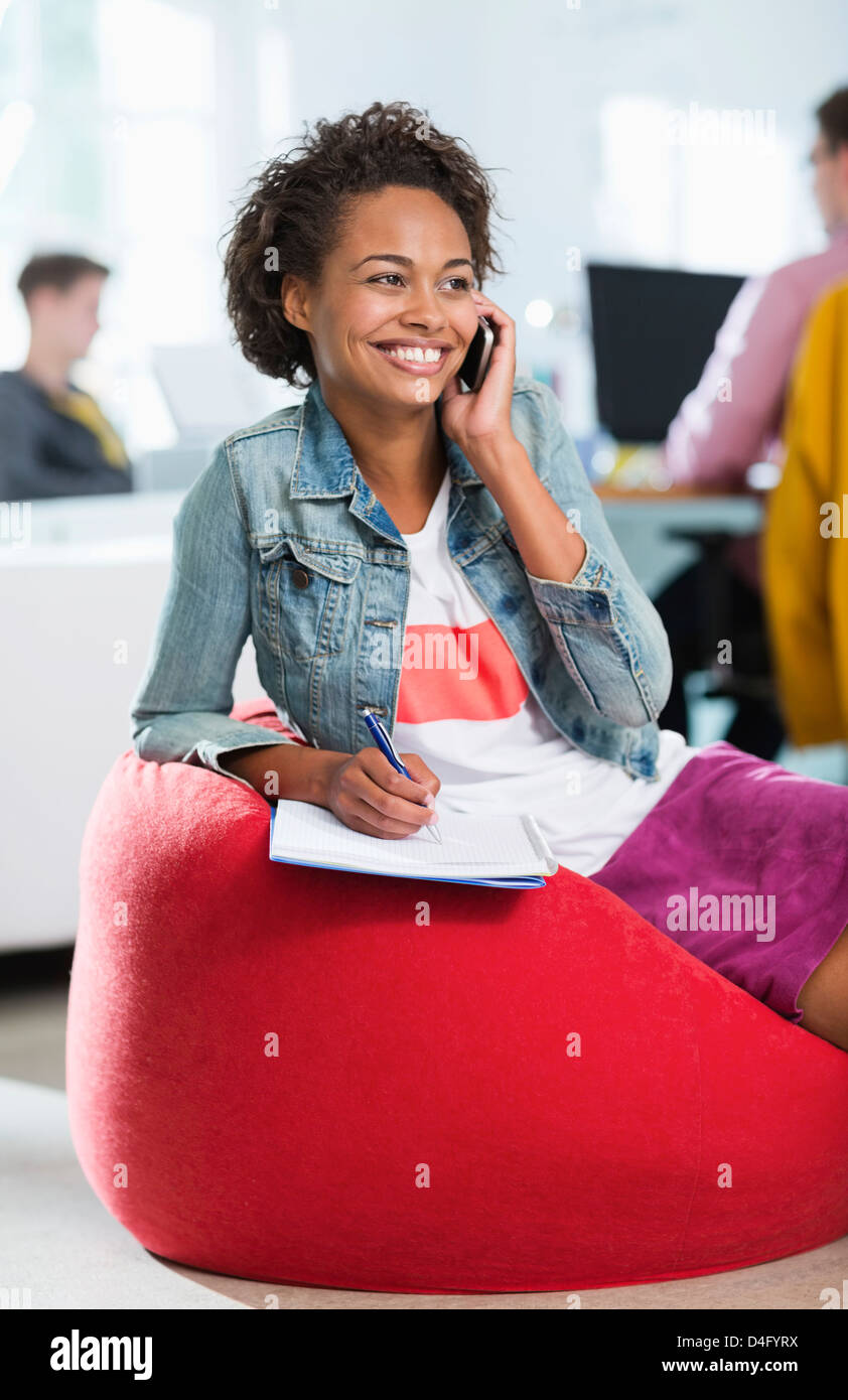 Businesswoman taking notes on phone in bean bag chair - Stock Image