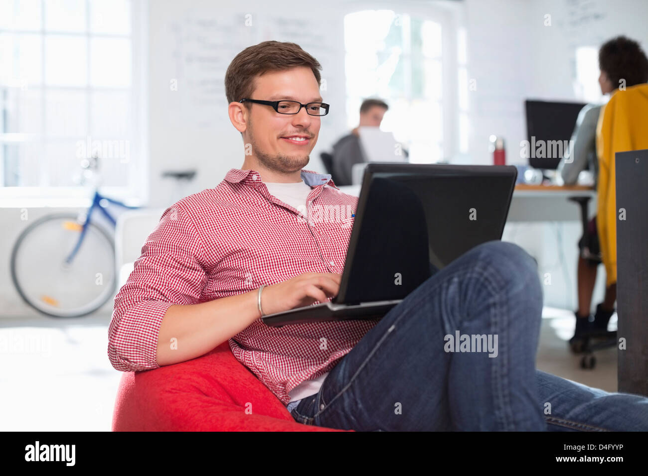 Businessman using laptop in bean bag chair in office - Stock Image