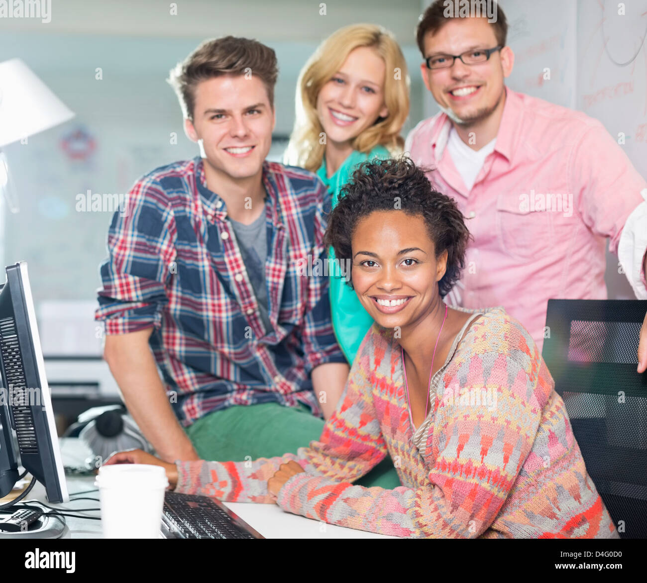 Business people smiling at desk - Stock Image