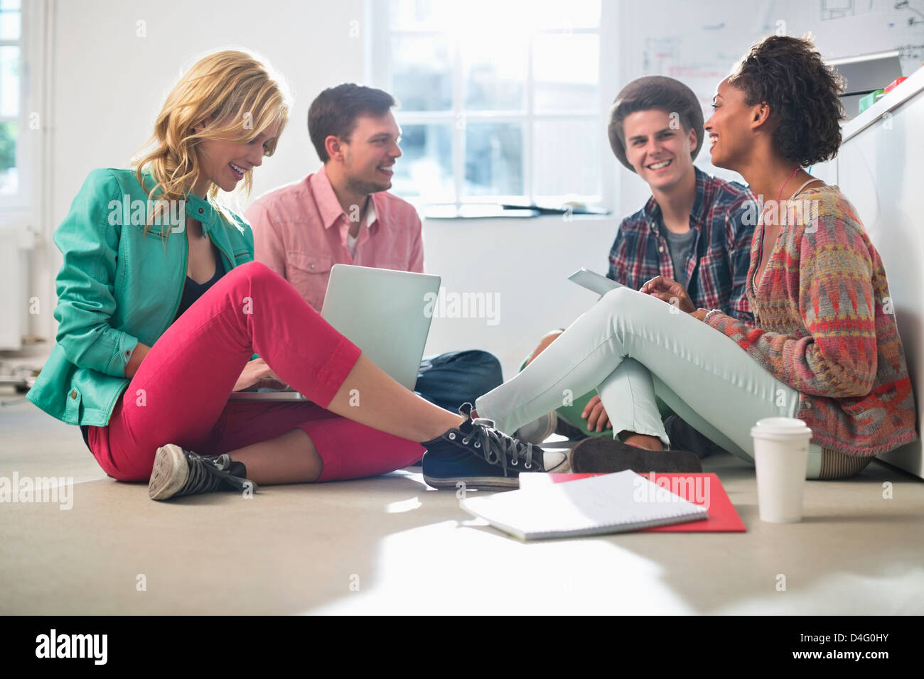 Business people talking on floor in office - Stock Image