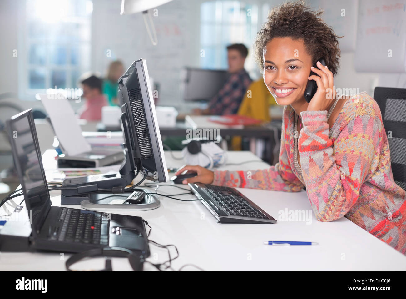 Businesswoman talking on phone at desk - Stock Image