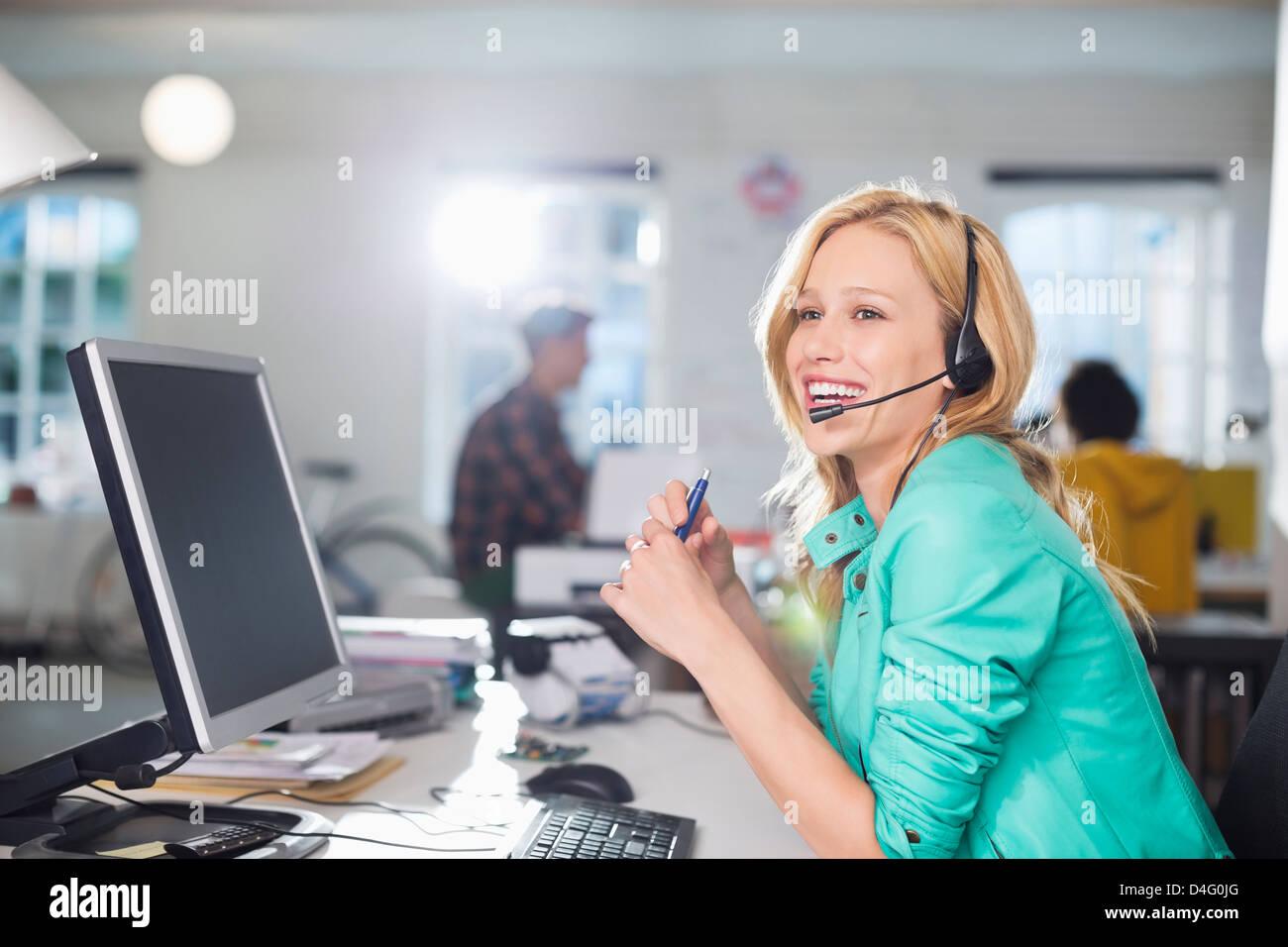 Businesswoman talking on headset at desk - Stock Image
