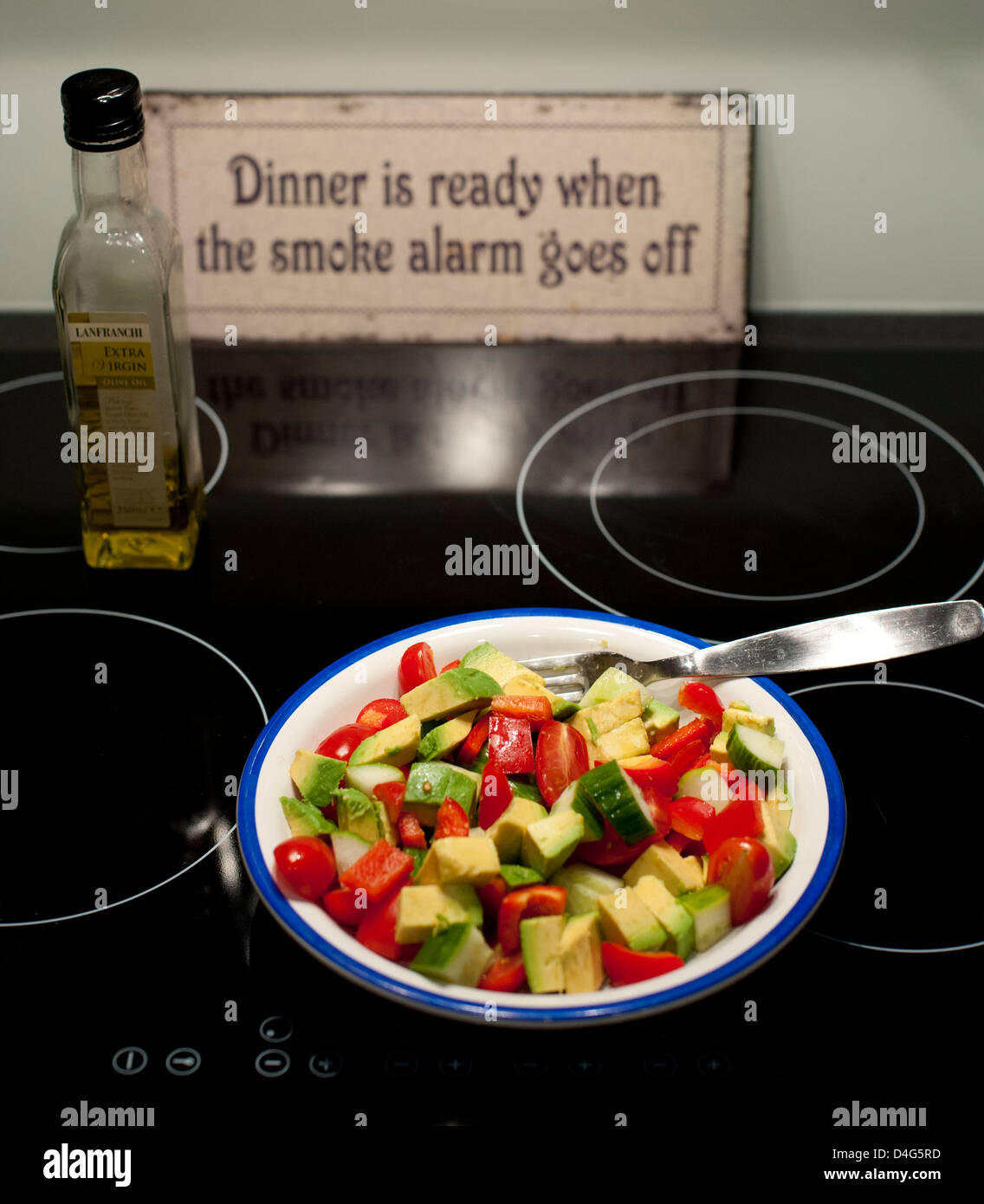 Healthy salad on a plate on a ceramic stove with a bottle of olive oil and a sign in the background - Stock Image