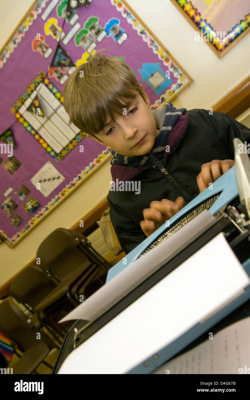 10 year old boy tapping out text on typewriter at a Charity Book Day in aid of a heart charity (Ben Williams Trust) - Stock Image