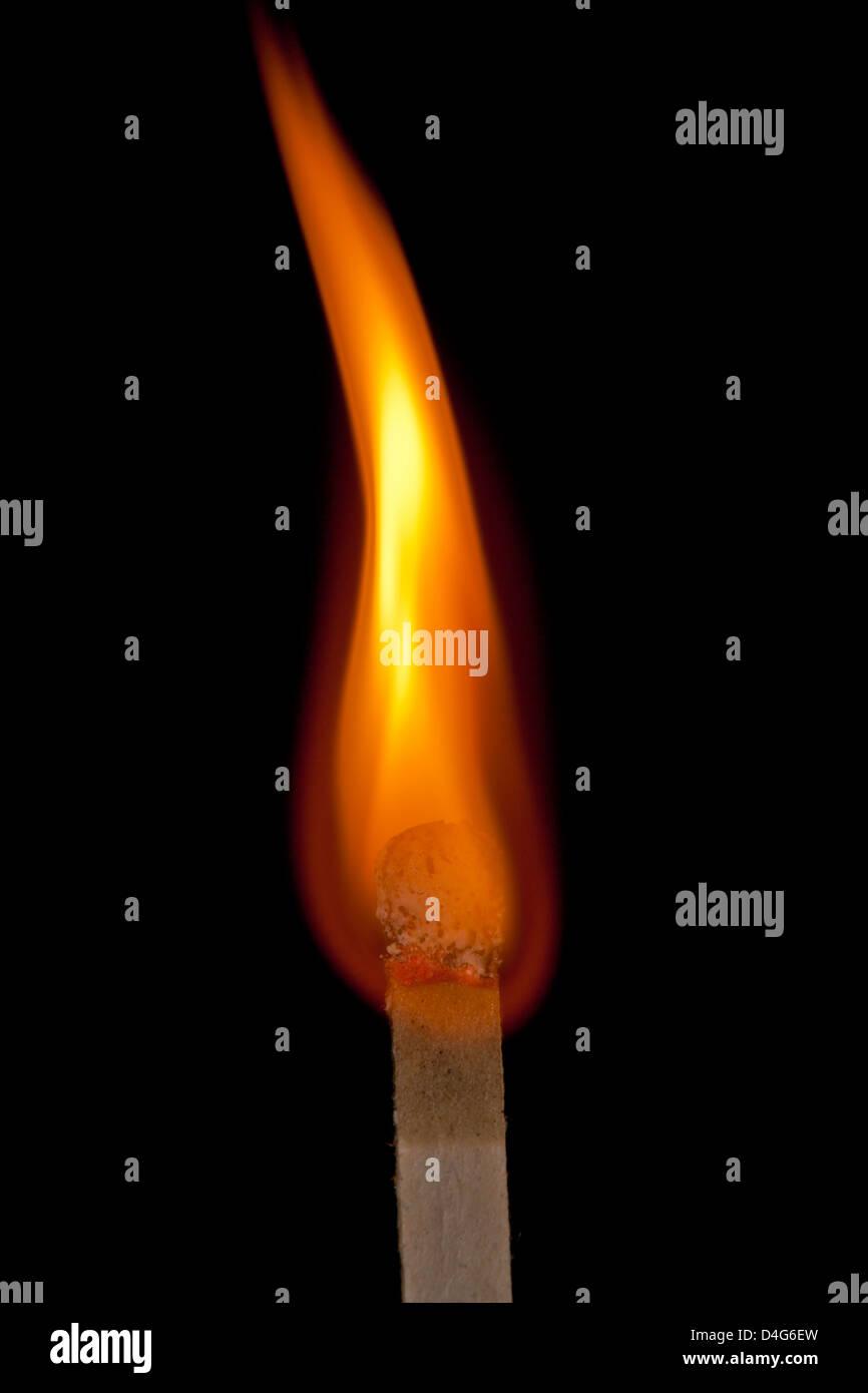 Flame burning on match against black background. - Stock Image