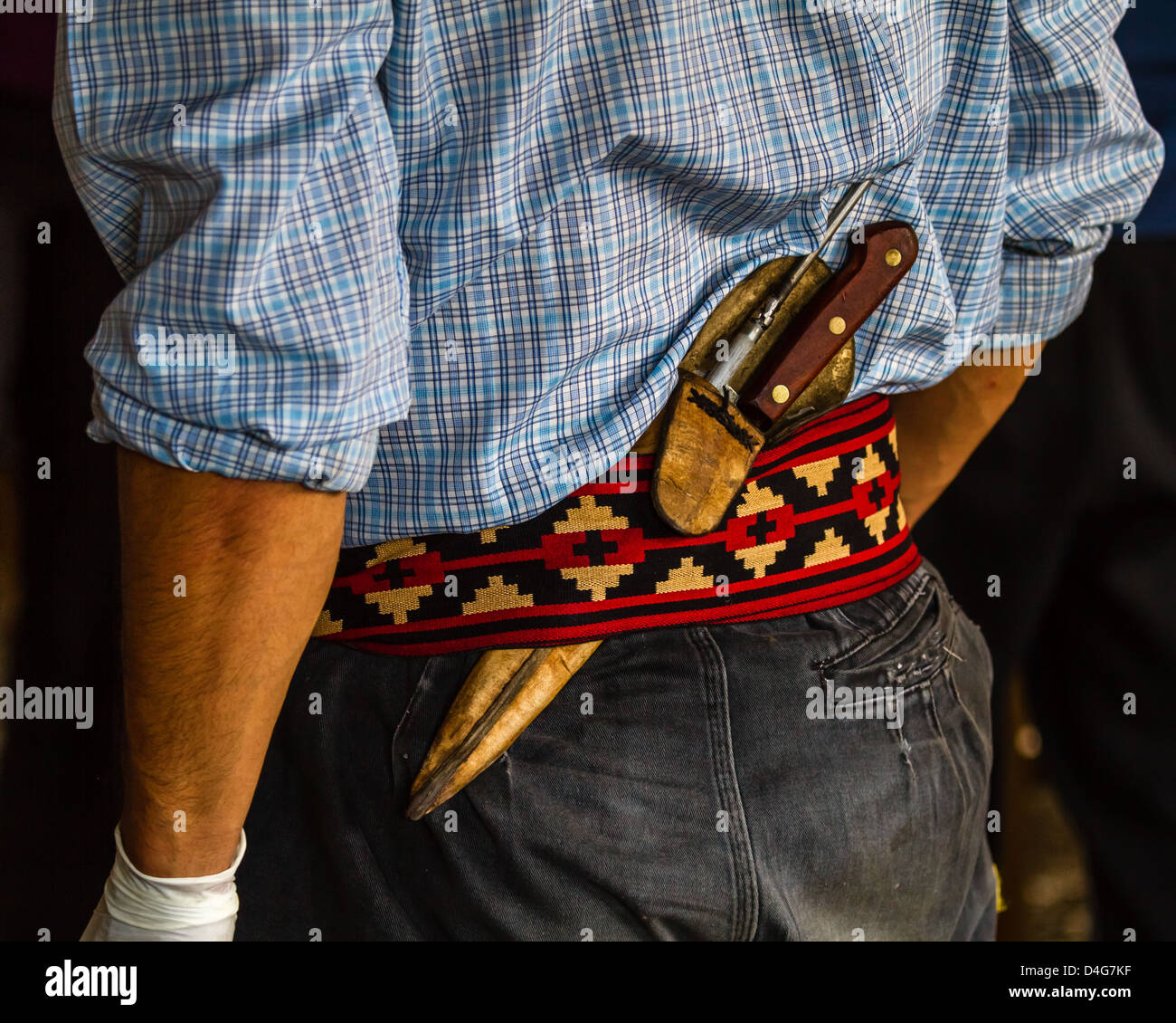 Detail of the belt of a Gaucho being worn on a person with a knife slipped in the back, Patagonia - Stock Image