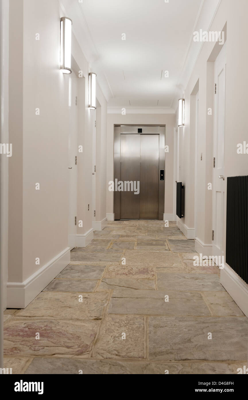 empty corridor with stone floor and closed metallic lift - Stock Image