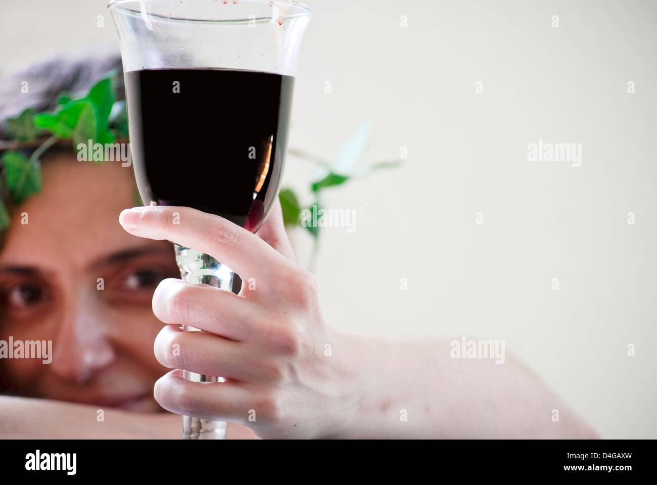 A female follower of Dionysus holding a glass of red wine Stock Photo