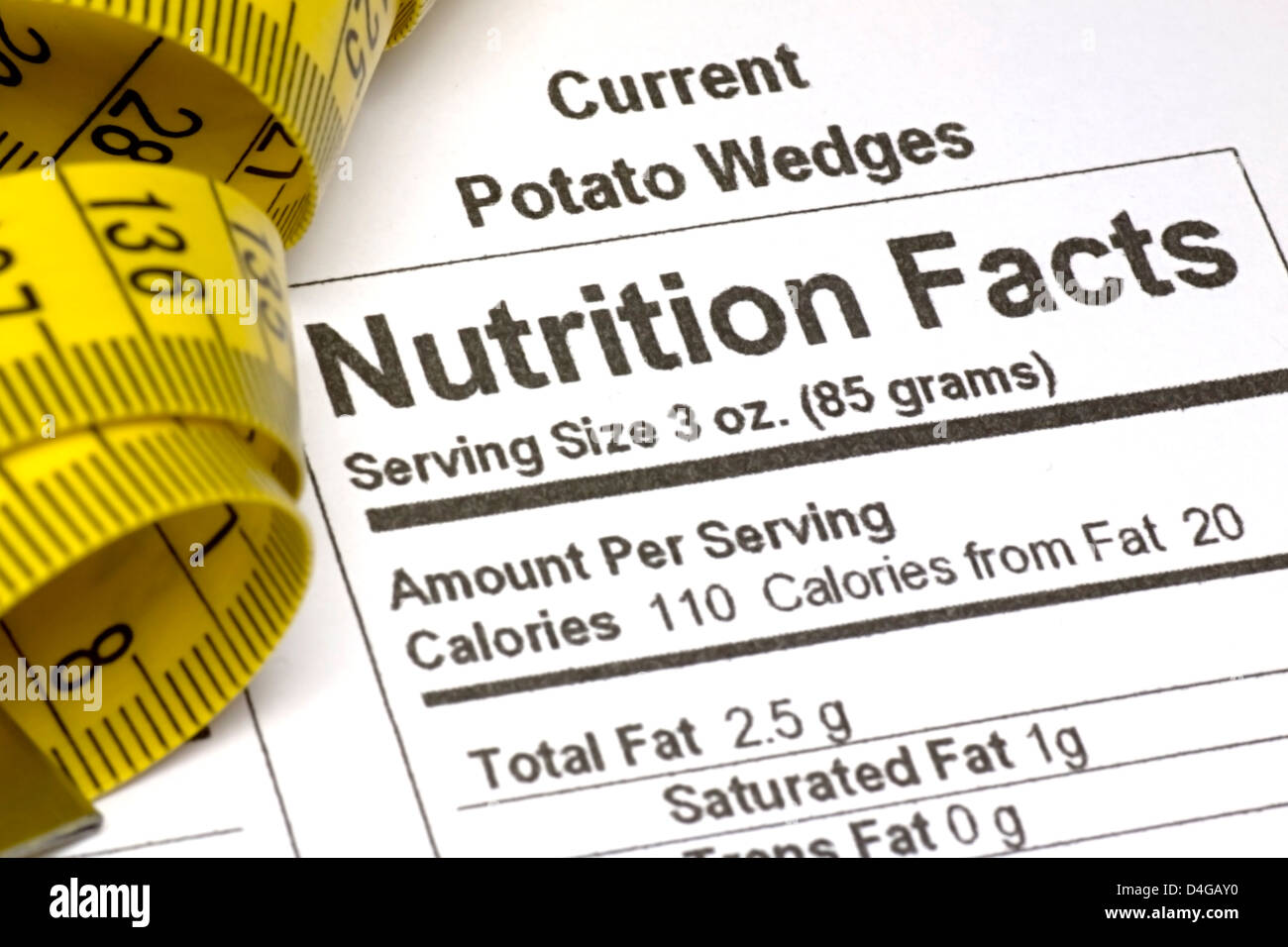 Yellow tape measure next to nutrition information on packaging in the USA - Stock Image