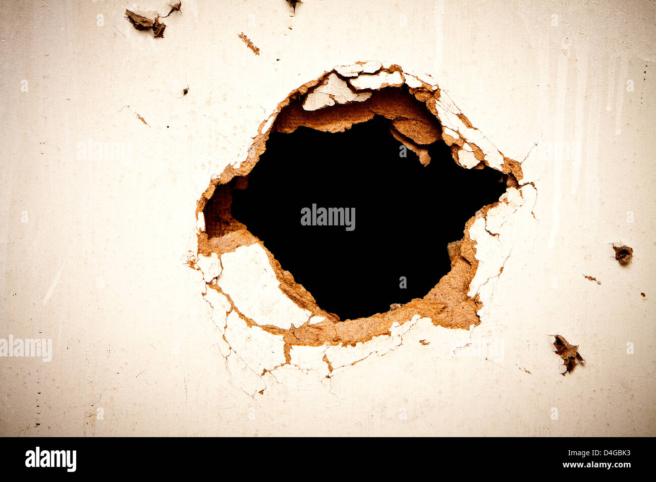 Hole in the fibreboard on black background. - Stock Image