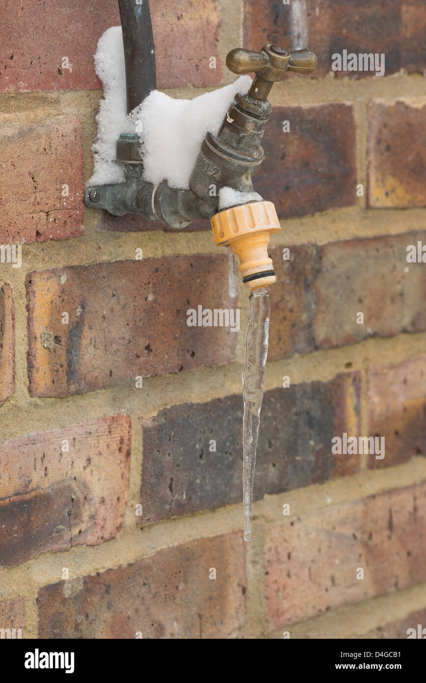 Leaking water tap frozen over in sub zero conditions icicle hanging from nozzle outside handle covered in snow - Stock Image