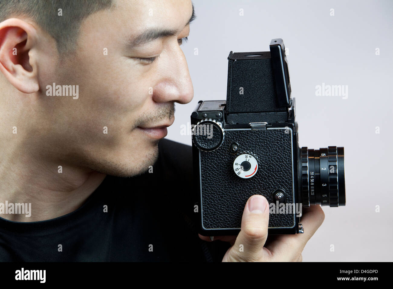 Young man taking photos with old-fashioned camera - Stock Image