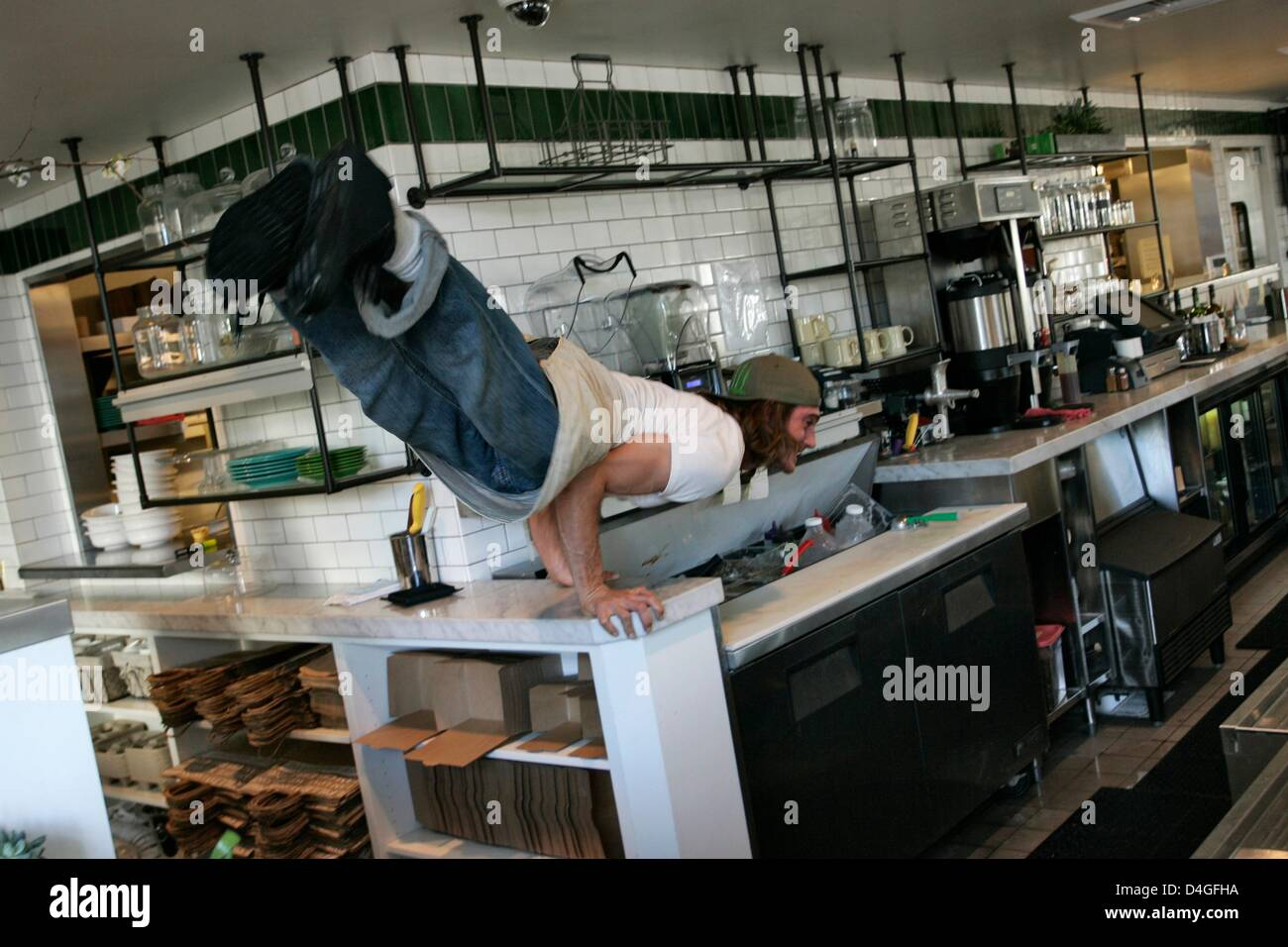 Feb. 3, 2013 - Venice Beach, California, U.S - Performing a yoga move on the juice bar is Joe Lubitsch, bartender - Stock Image