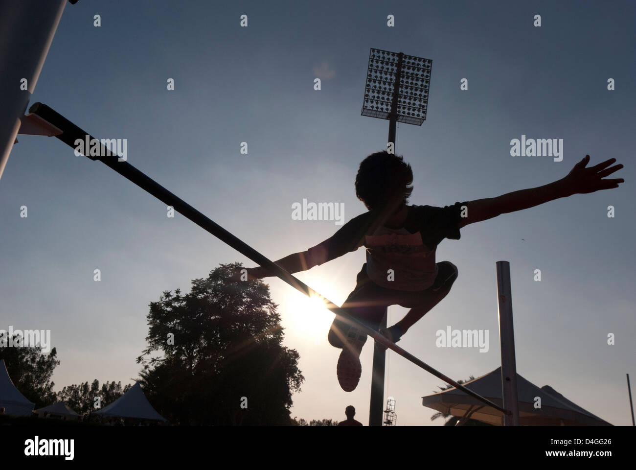 The silhouette of a boy participating in the high jump. - Stock Image
