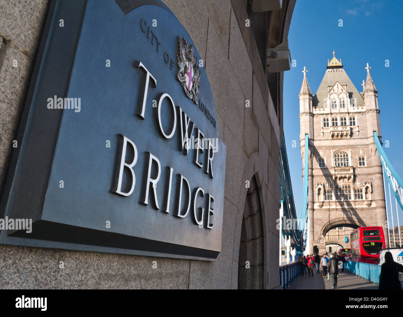 Tower Bridge and name plaque with traditional red bus in background Southwark London UK - Stock Image