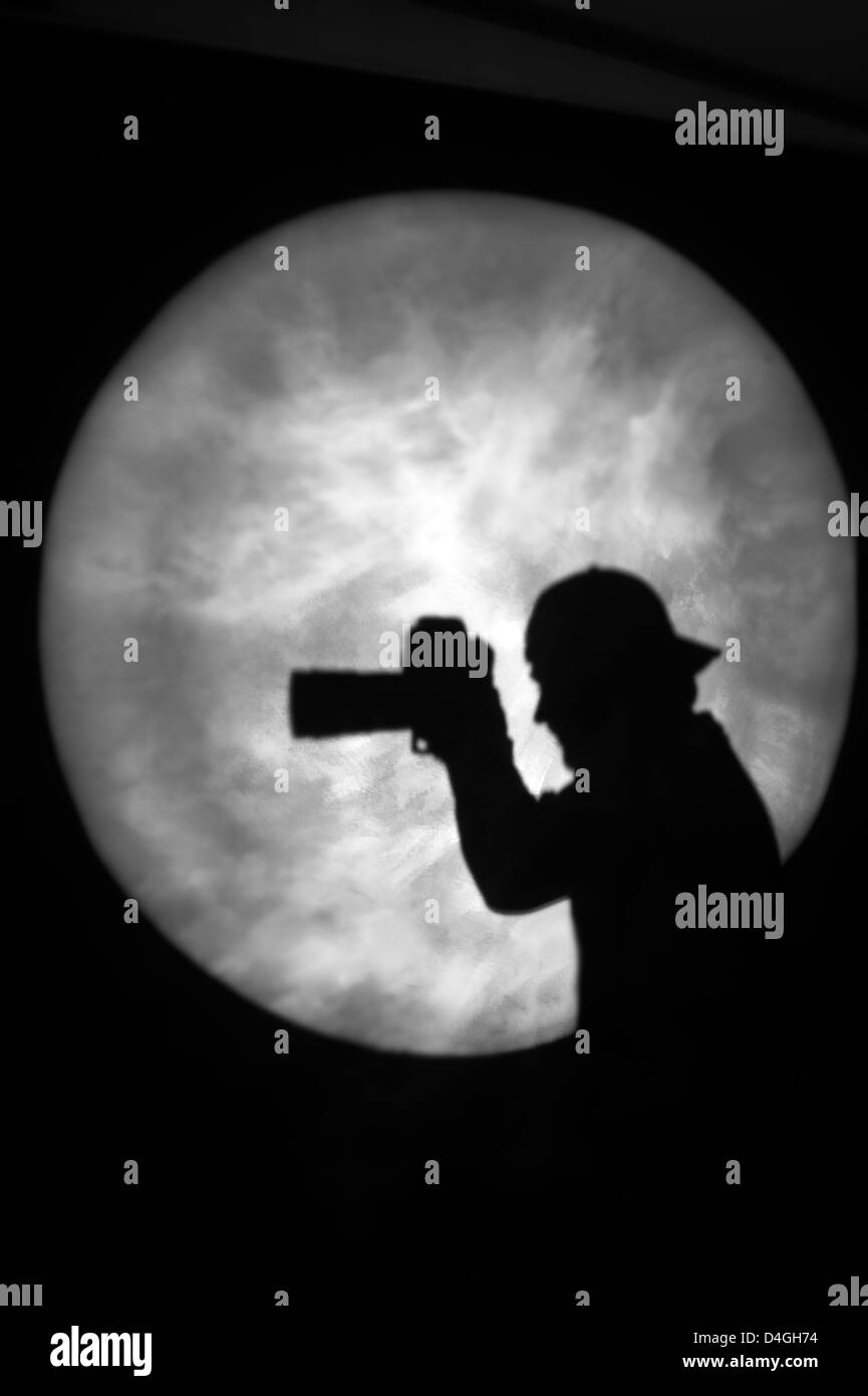 Silhouette of a man holding a camera in spotlight or moonlight (model released) - Stock Image