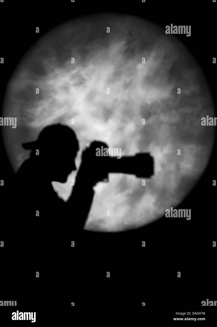 Silhouette of a man holding a camera in spotlight or moonlight (model released) Stock Photo
