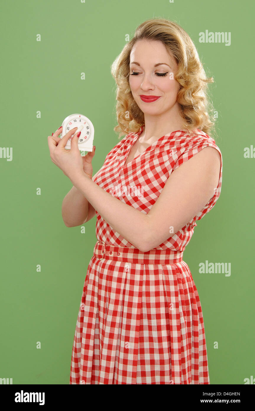 Woman adjusting cooker timer - Stock Image