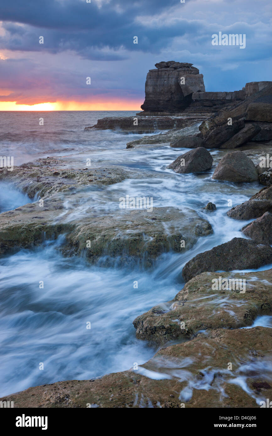 Waves crash against the rocky coast of Portland Bill at sunset. Isle of Portland, Dorset, England. Spring (April) - Stock Image