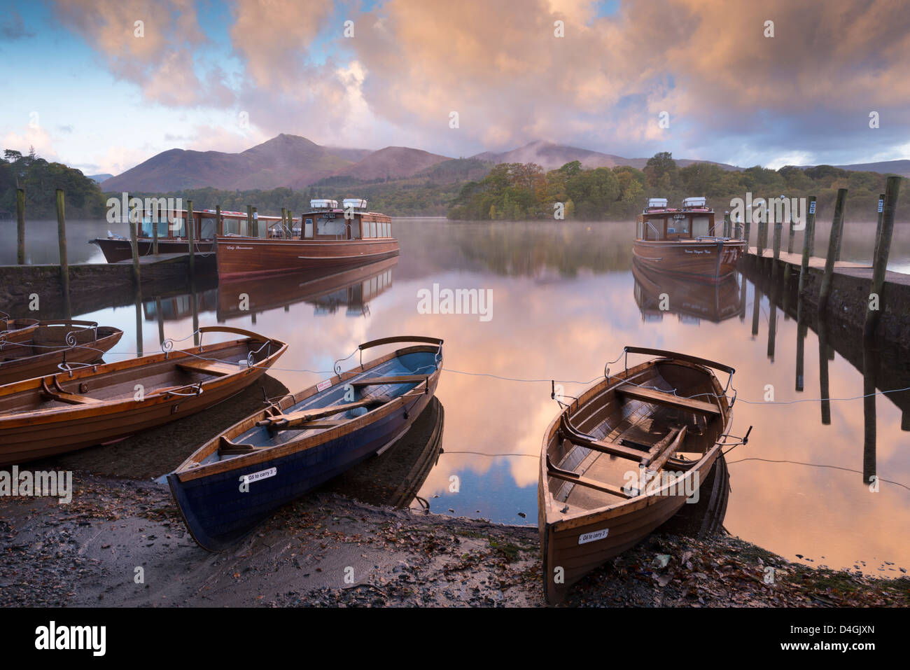 Boats and jetties near Friars Crag at dawn, Derwent Water, Lake District, Cumbria, England. Autumn (October) 2012. - Stock Image