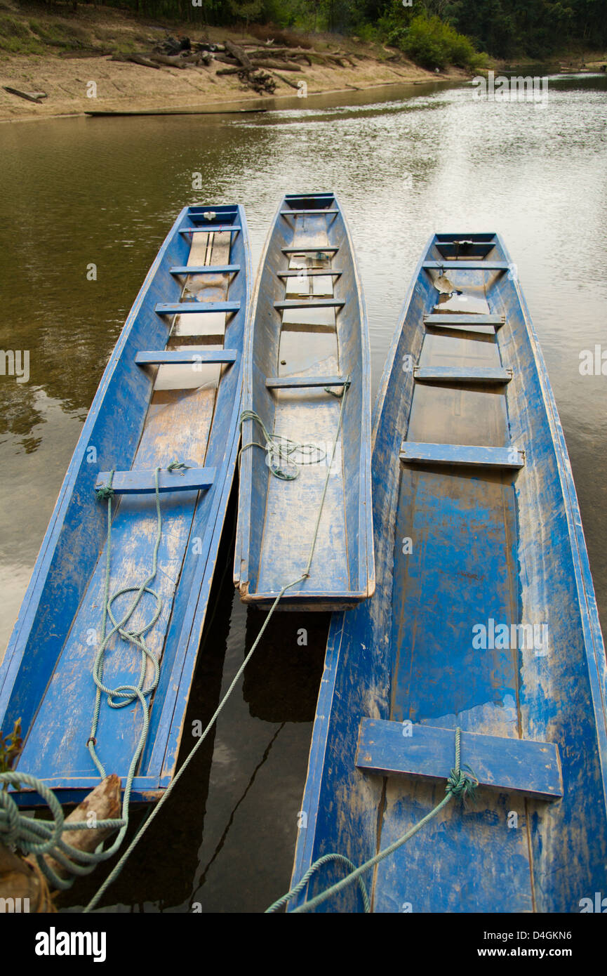 Three blue boats sit anchored by the shore - Stock Image